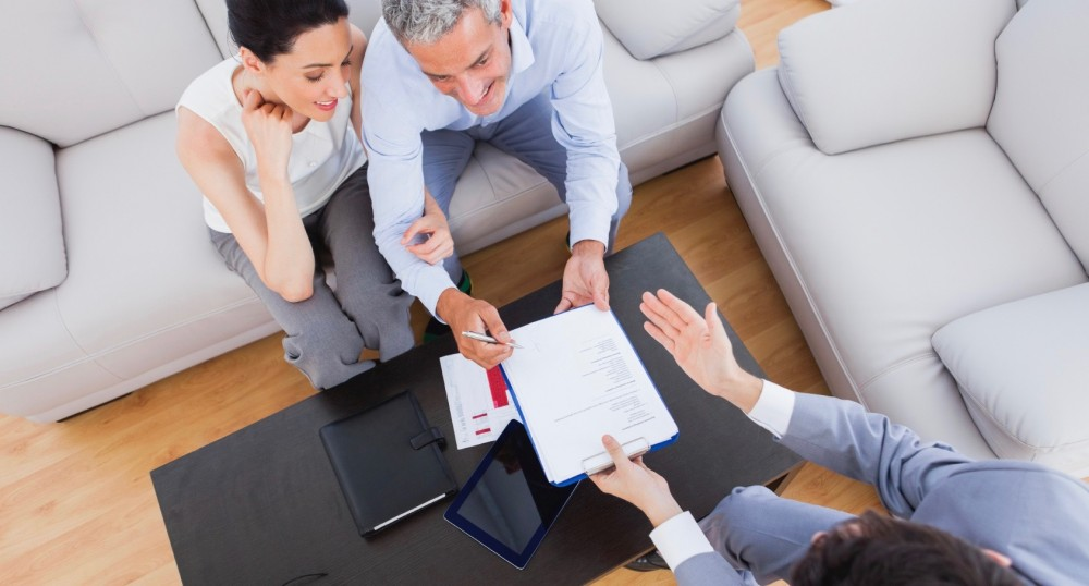 Salesman showing contract to couple who are about to sign at home on couch
